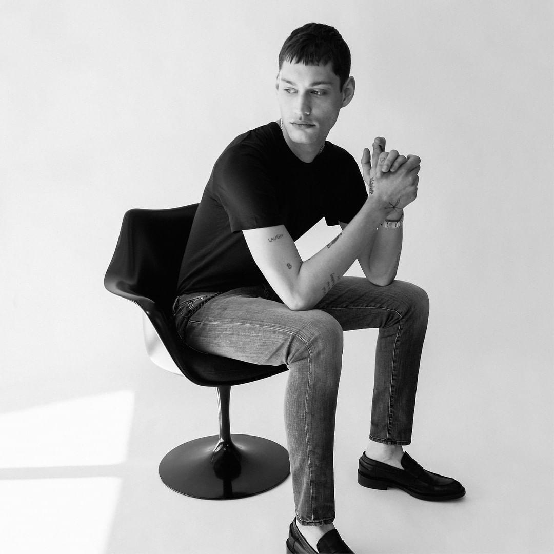 A man sitting in a chair in Tramarossa jeans