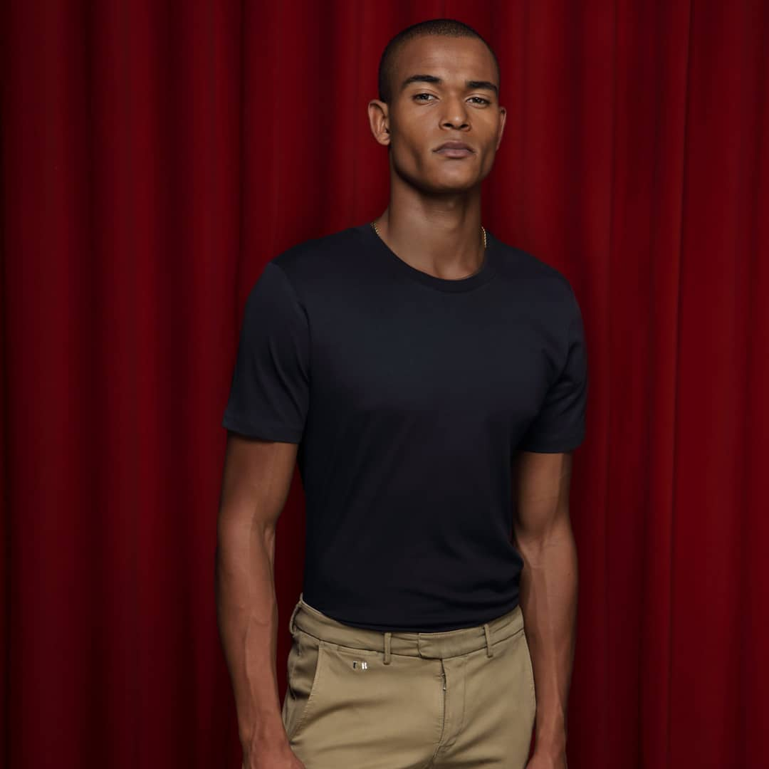 Model wearing tramarossa trousers infront of a red curtain