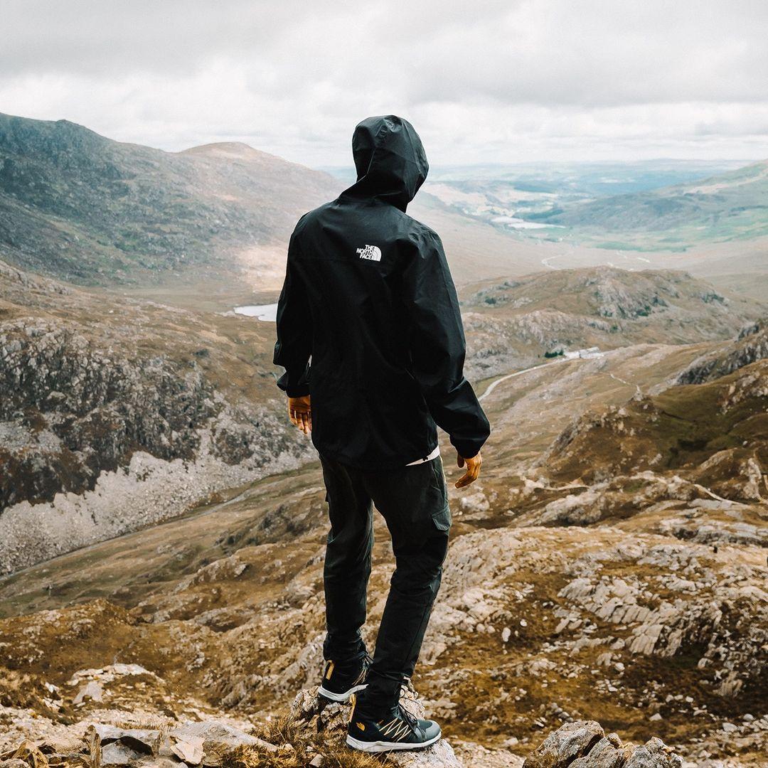 man climbing mountain wearing tnf