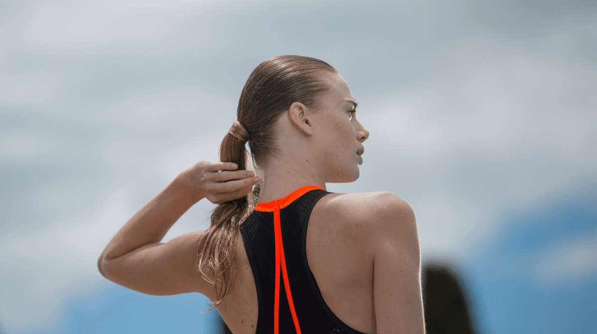 A woman feeling her hair after swimming