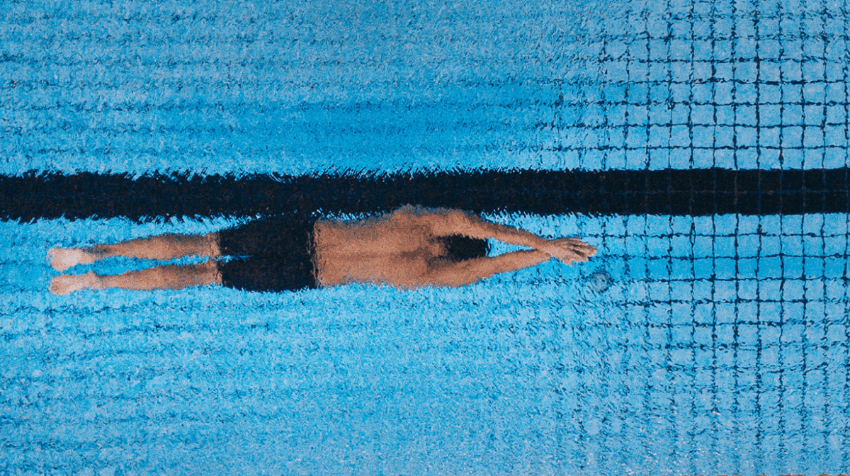 A man swimming underwater in a swimming pool