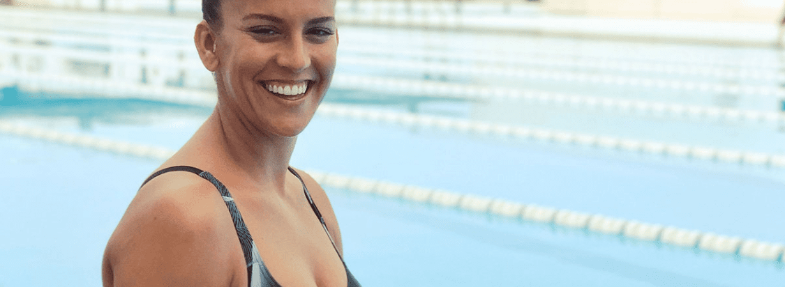 A woman smiling after completing a workout in a swimming pool