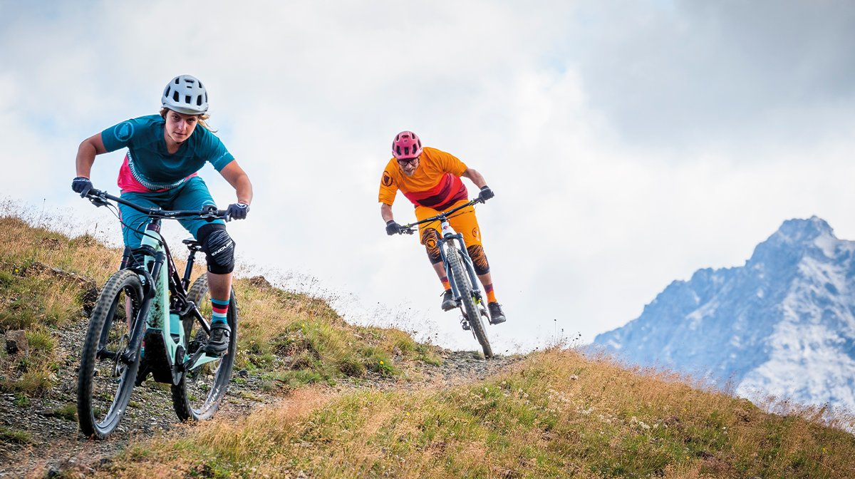 Two mountain bikers speed by