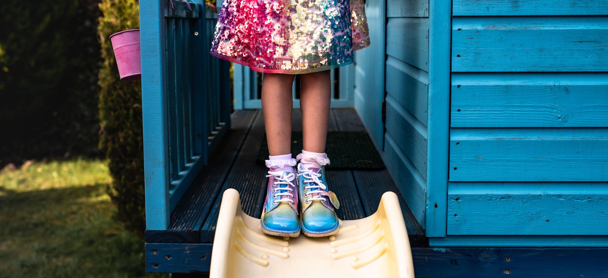 Child's shoes pose on top of slide
