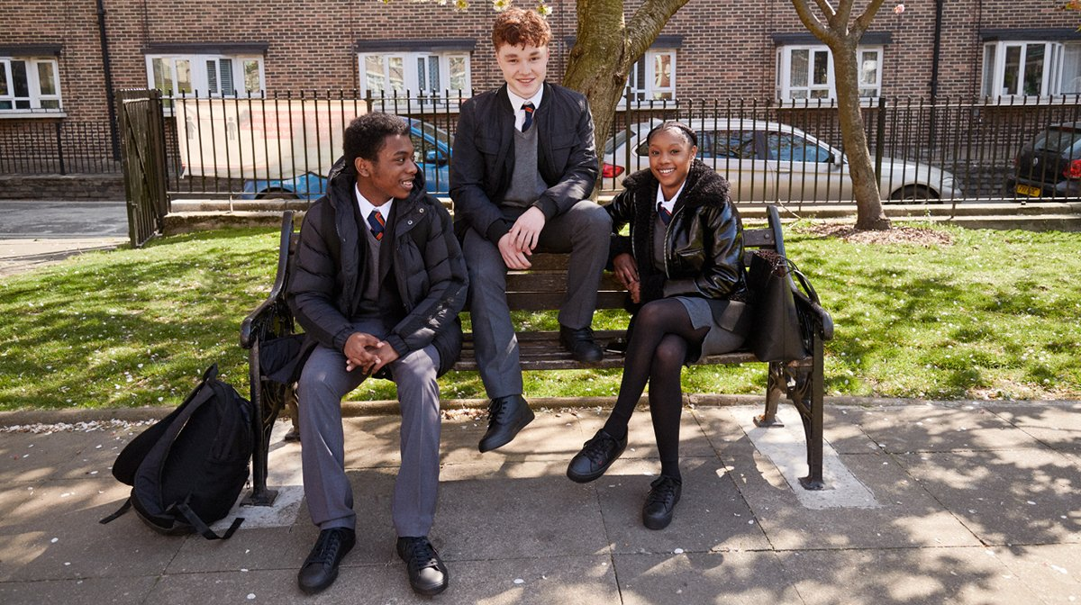 3 kids pose on a bench together