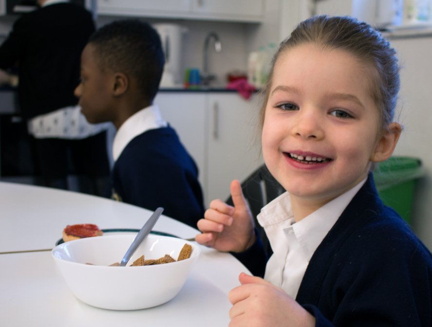 Young girl smiles with breakfast infront of her