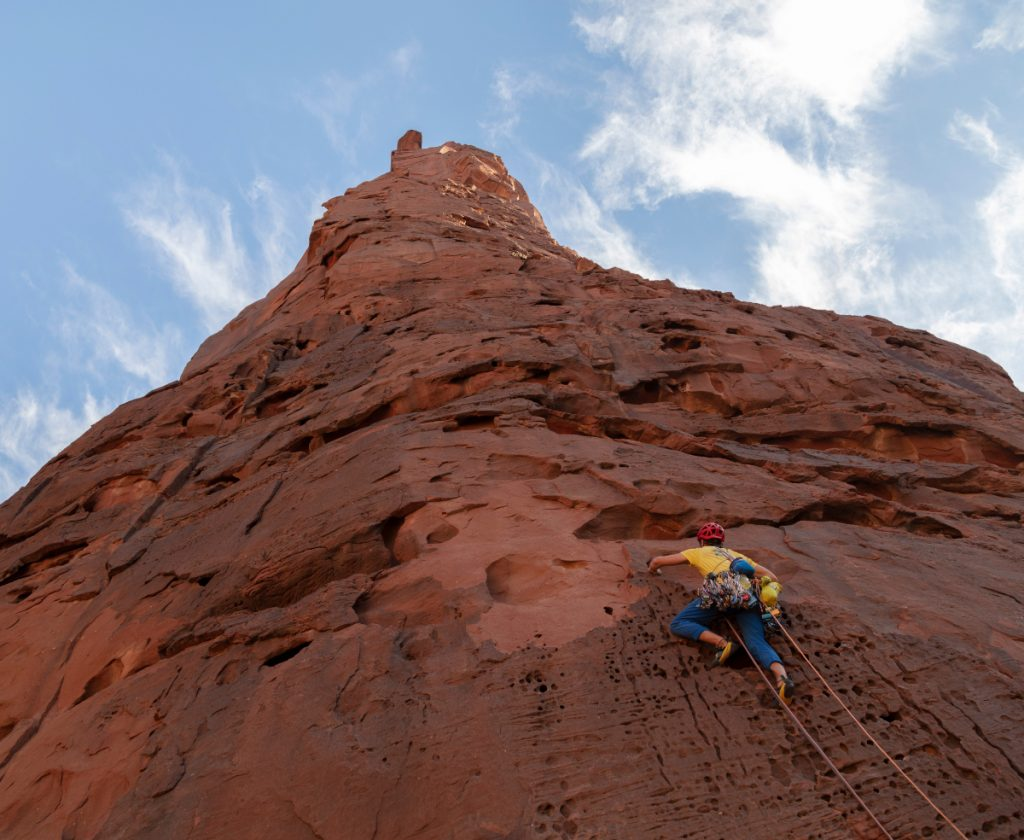 Arabian tower stretches high into the sky, with climber gripping onto the side