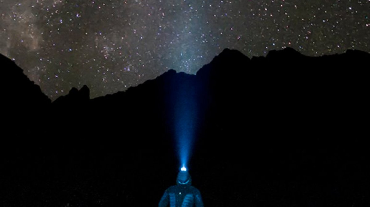 A man wearing a torch helmet while on a night navigation walk