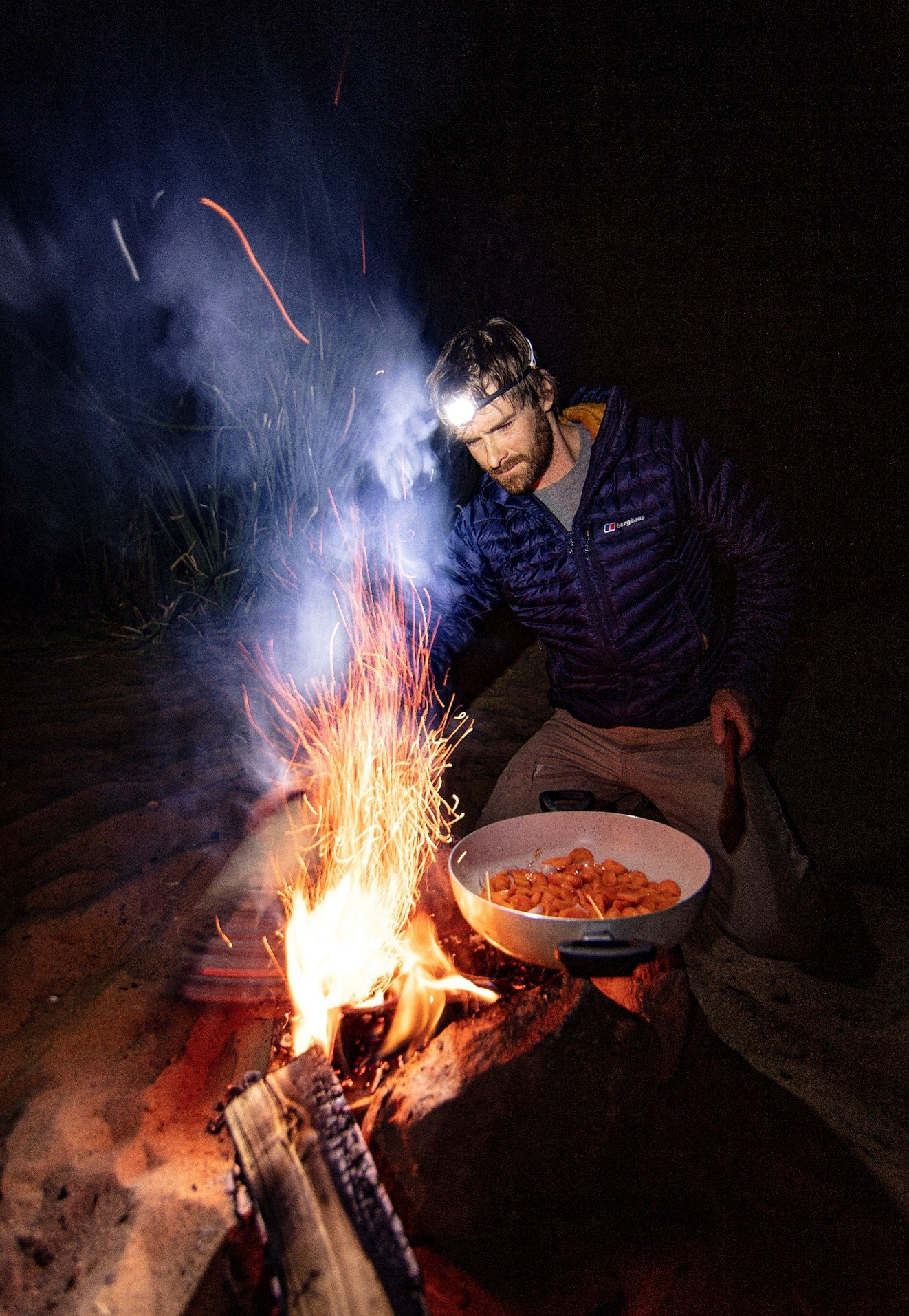 Man cooks on open flame and sparks leap high