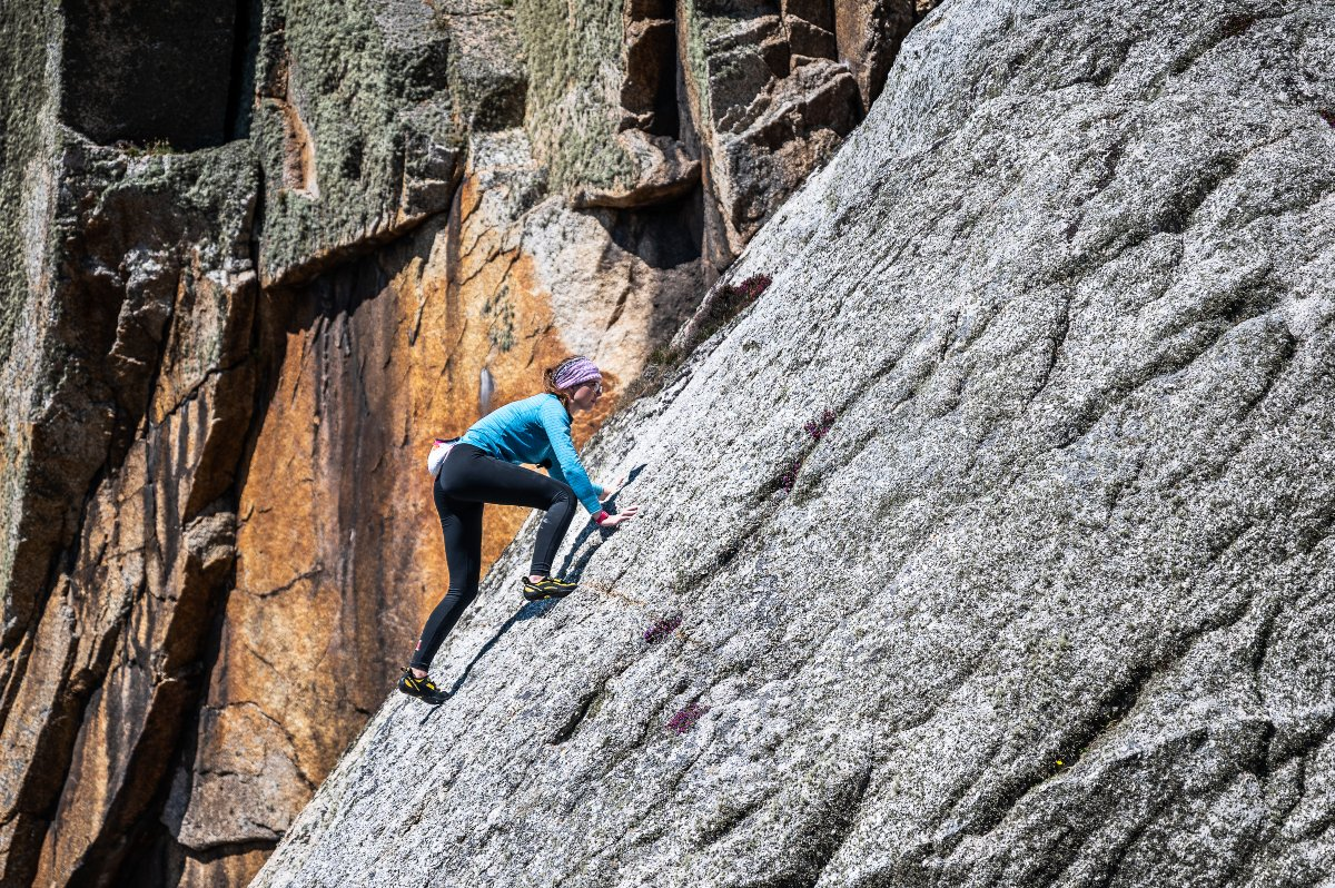 Climbers ascends steep rock face