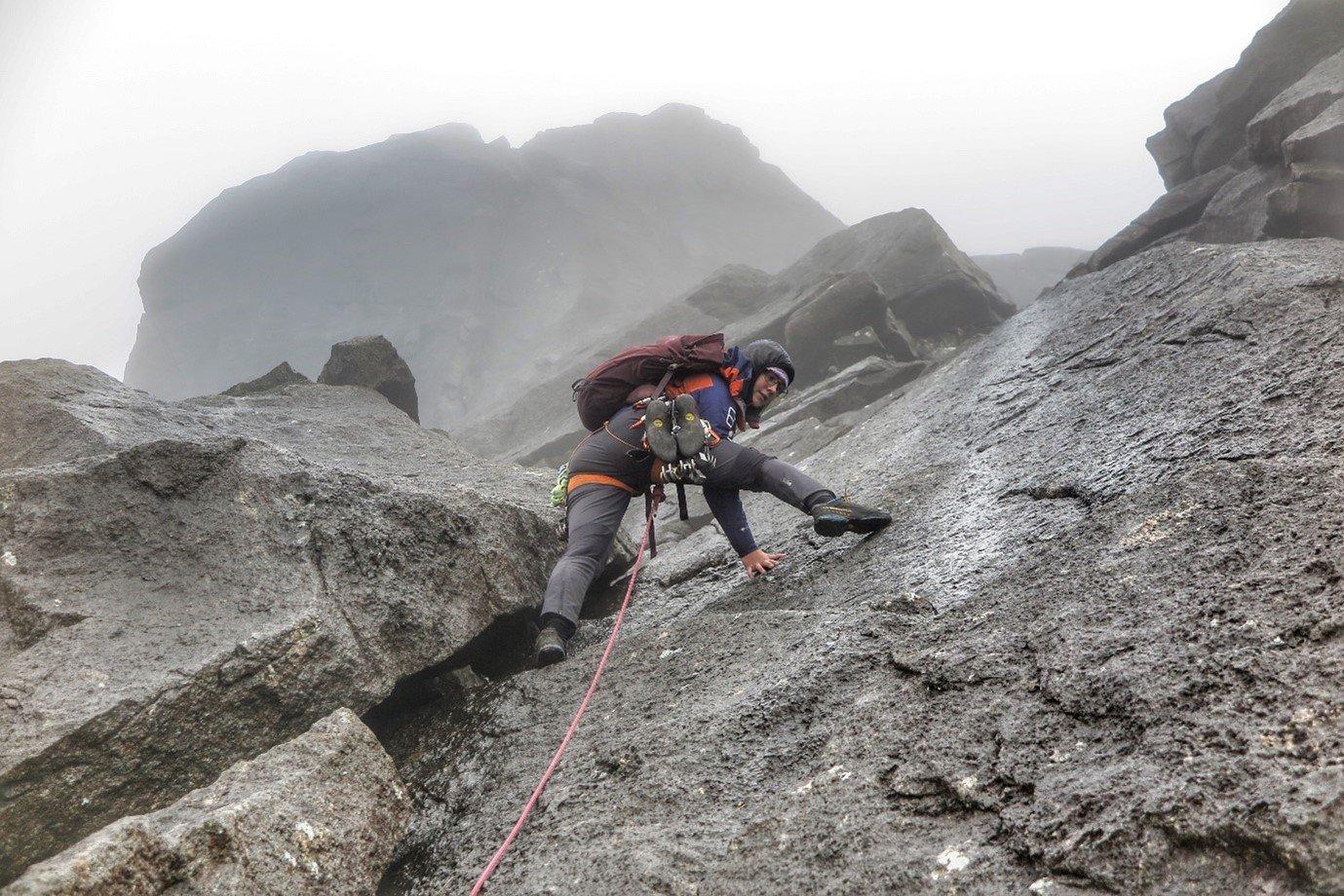 Anna climbing steep rock in Berghaus waterproof clothing