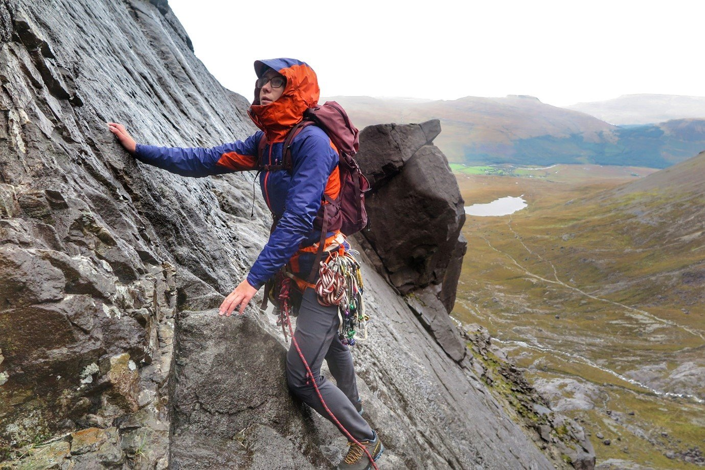 Anna stands on cliff in orange and purple Berghaus waterproofs