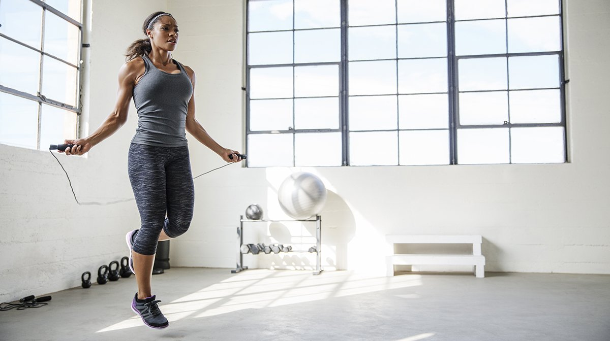 Woman skipping in white studio in workout clothes