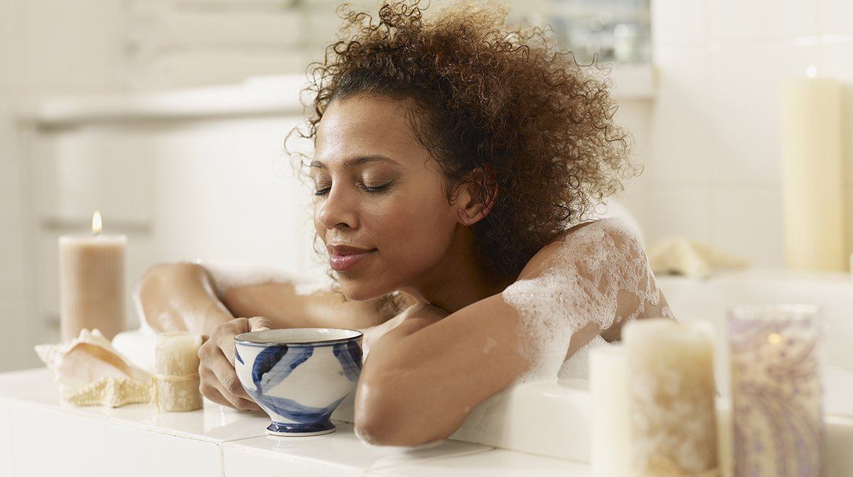 Woman relaxes in the bath with candles and cup of tea
