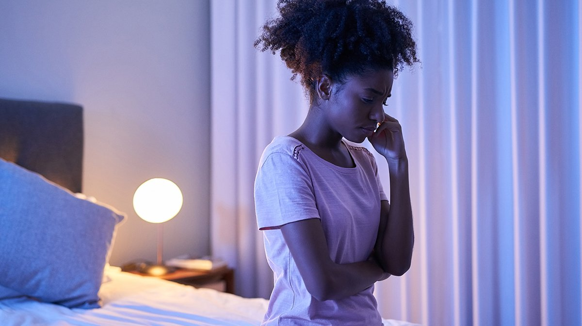 Woman sits awake worry at end of bed at night