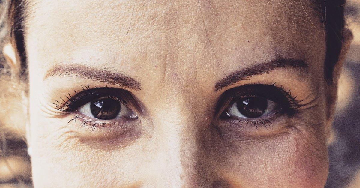 close up womans brown eyes makeup