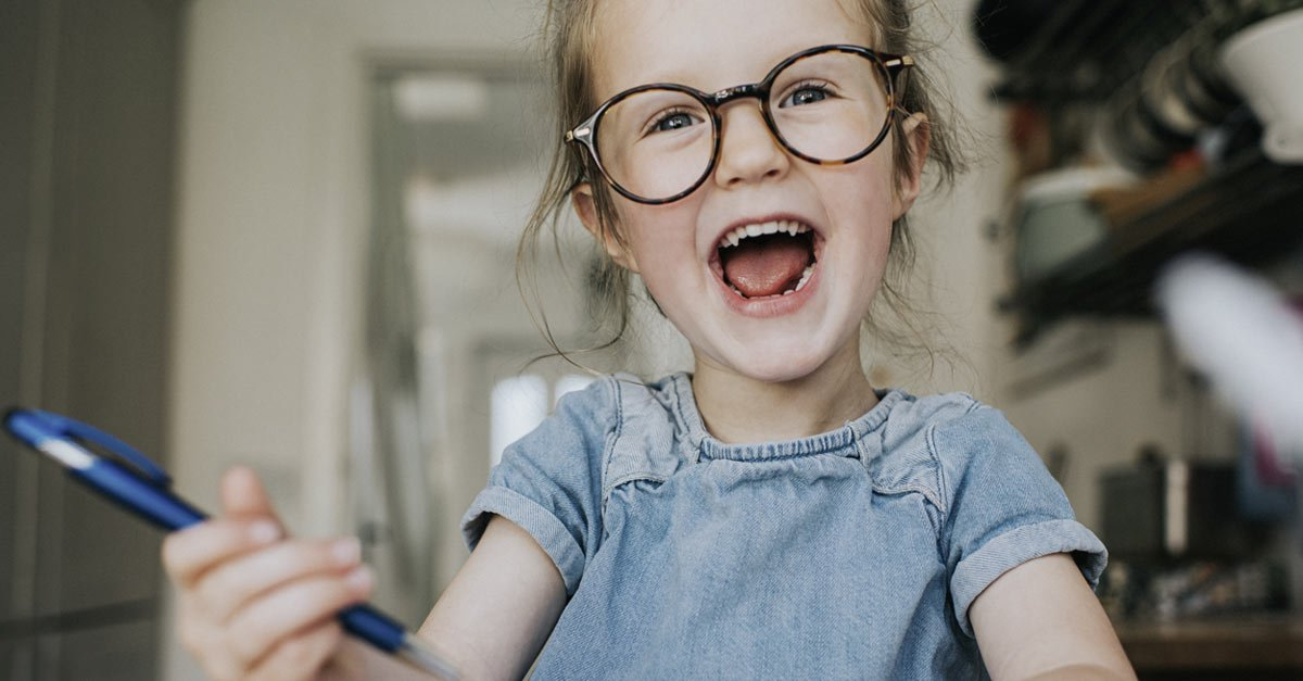 Little girl wearing glasses laughing and smiling