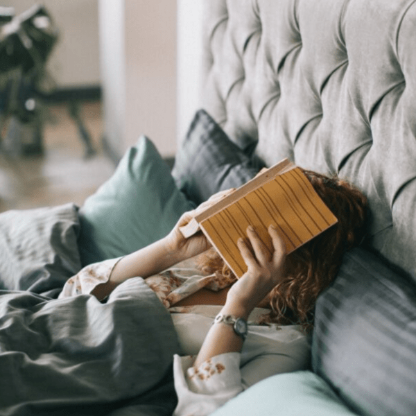 girl in bed with book over her head