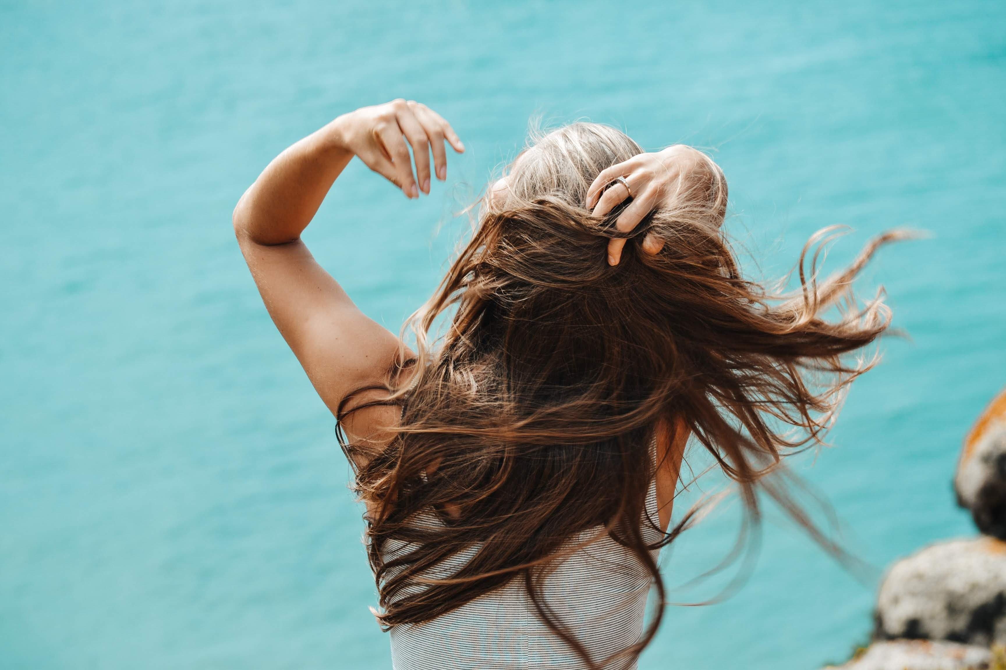 Frau fährt sich durch die Haare
