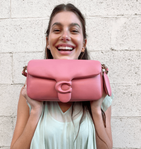 Model holding a pink handbag in her hands