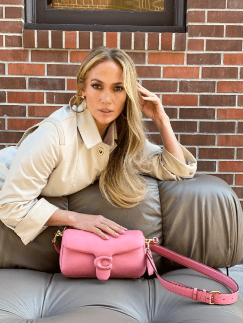 Jlo on a couch with a pink handbag