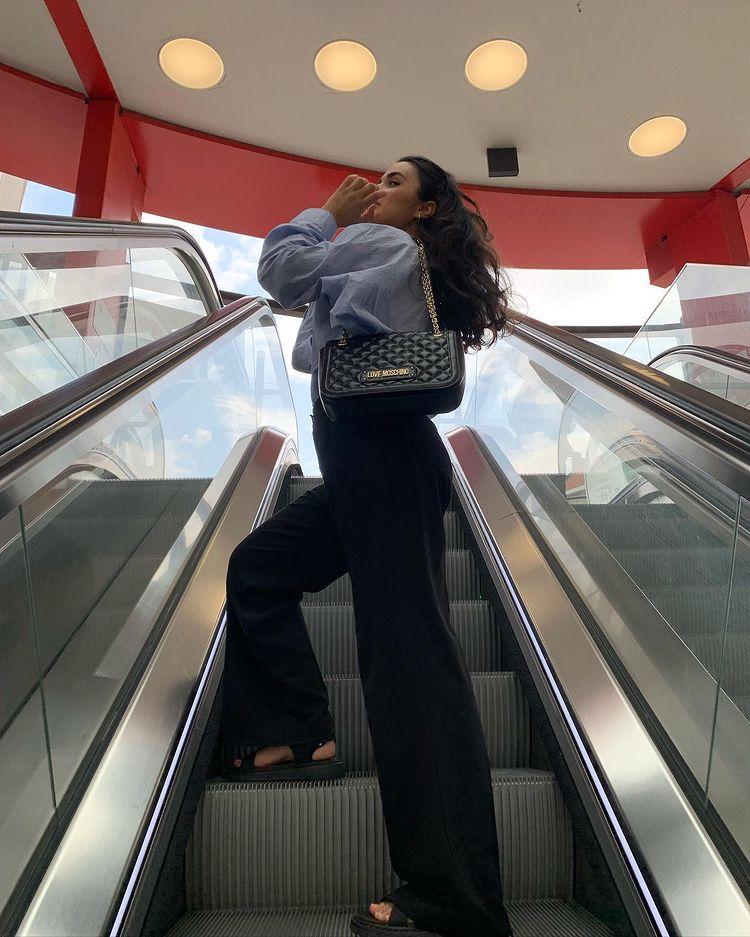 Women wearing love moschino bag standing on the escalators