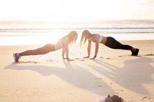Women planking together on the beach