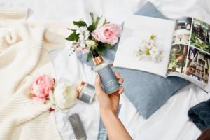 Hand holding up grow gorgeous hair defence spray with flowers and magazine in background
