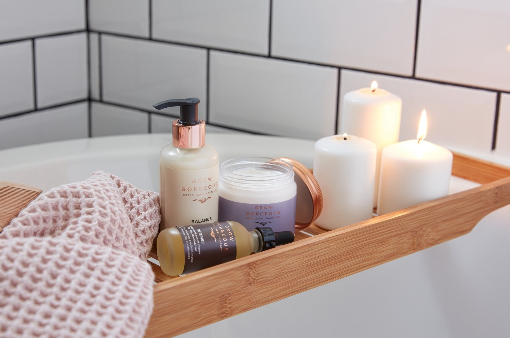 Grow Gorgeous Balance Split Ends Treatment, Intense Hair Growth Serum and Repair Rescue Mask on a bath rack shelf with pillar candles and a pink towel in a bathroom with white subway tiles