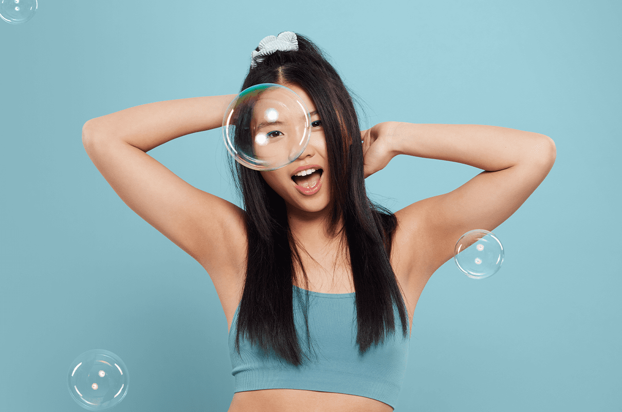Woman with arms up dancing, with a blue background and bubbles