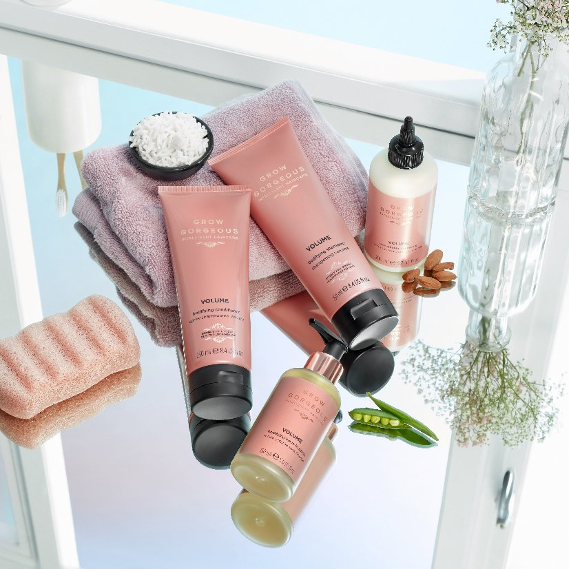Grow Gorgeous Volume range placed on a mirror with towel and soap