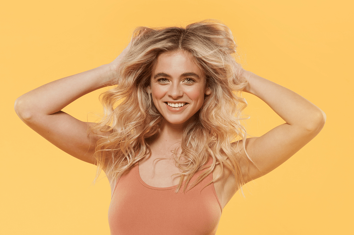 Bright yellow background, smiling woman with blonde hair pushing hair up with hands, embracing strand texture.