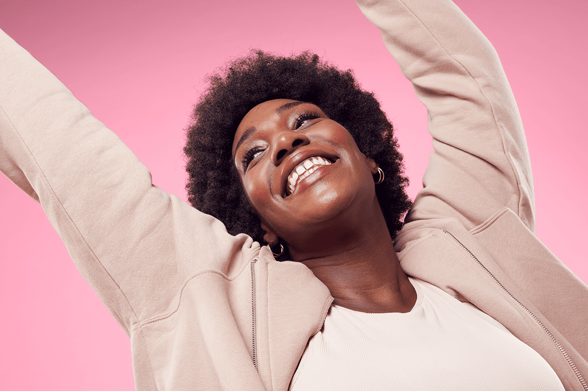 Woman smiling with hands in the air, pink background with afro-textured hair, expressing joy and self-confidence.