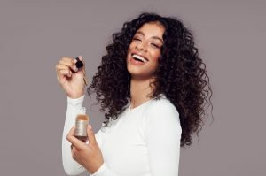 Woman with curly hair holding up the Grow Gorgeous Growth Serum