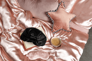Satin sleep cap on top of pink satin bedding with a pink starred pillow, coffee and book next to it.