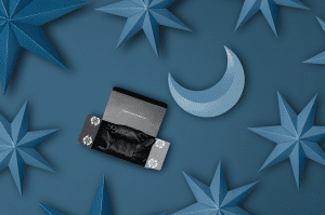 Black satin sleep bonnet in its package on top of a navy background with blue moon and stars.