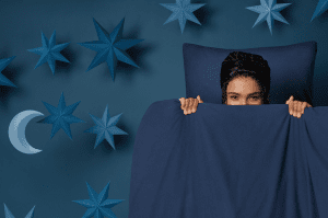 Woman wearing a black satin head wrap for sleeping with navy bedding and blue background containing blue stars and moon.