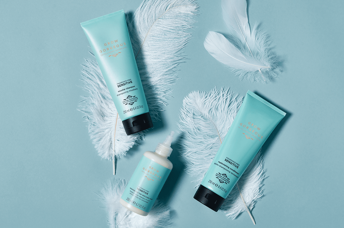 The sulfate-free Grow Gorgeous sensitive range, containing three blue bottles for treating a sensitive scalp placed on top of feathers.