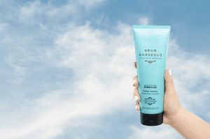 A hand holding up in the clouds the Grow Gorgeous dandruff fragrance-free and dermatologically tested sensitive replenishing conditioner.