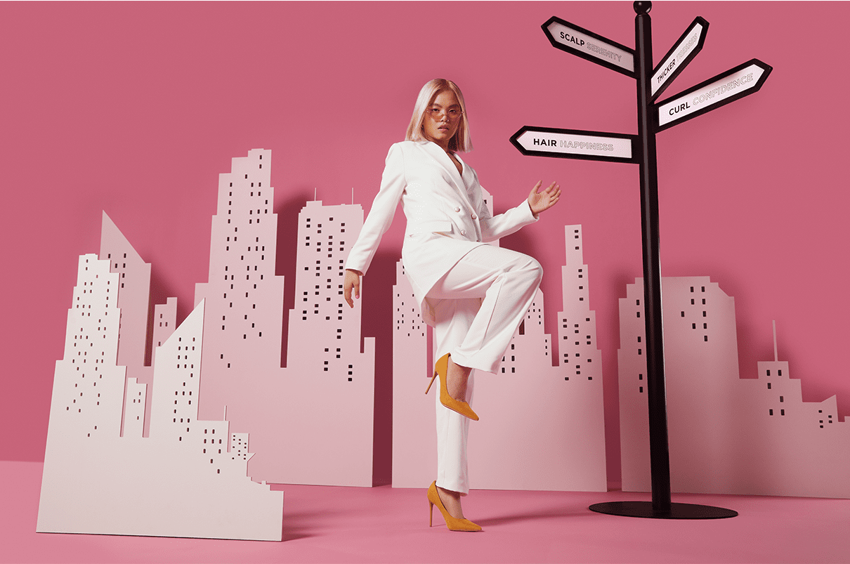 Woman with blonde straight hair, wearing a pink suit walking past a pink city skyline.