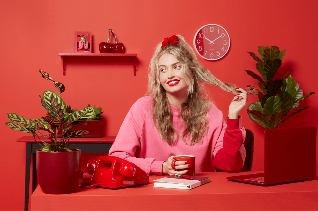Woman with blonde wavy hair sitting in her red home office surrounded by plants and a laptop.