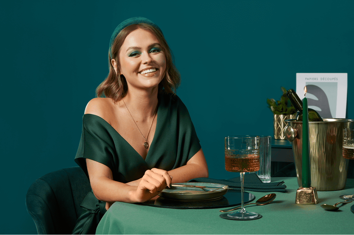 A woman with short straight hair sitting at a table for dinner with a glass of wine smiling