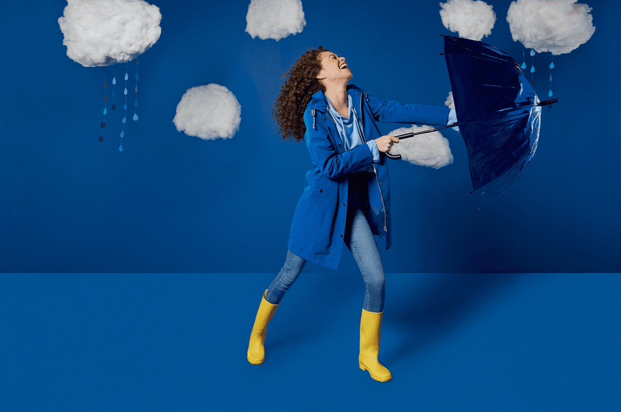 Woman with long curly hair wearing a blue raincoat and yellow welly's, holding up a blue umbrella fighting the rain.