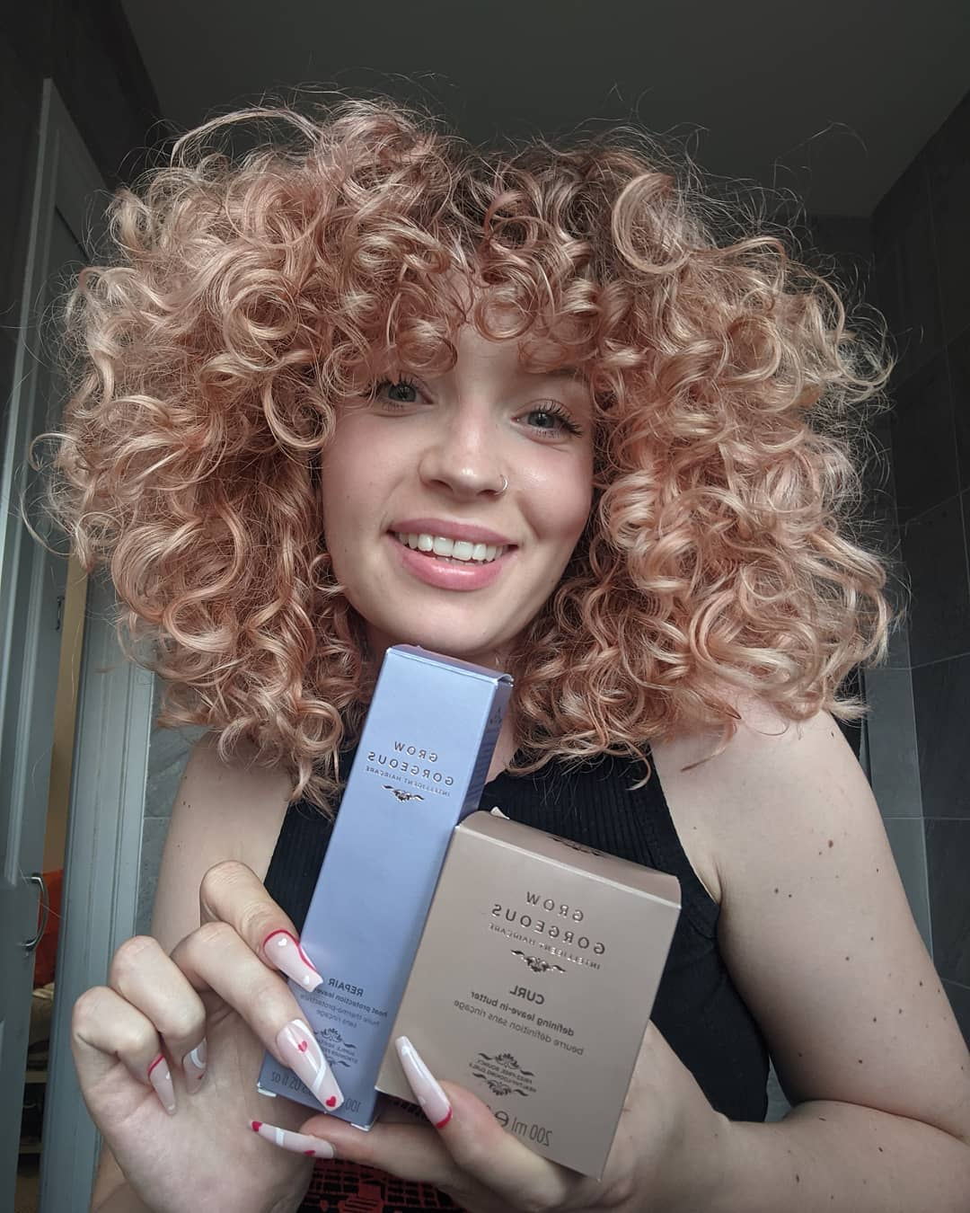 Woman with short blonde curly hair holding up two Grow Gorgeous products; the curl butter and repair oil.