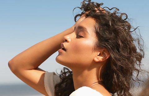 Model running her hands through her hair in wind