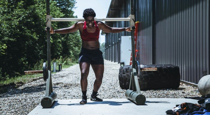 woman lifting heavy weight outside