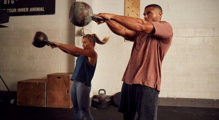 man and woman performing kettlebell swings in raw collection