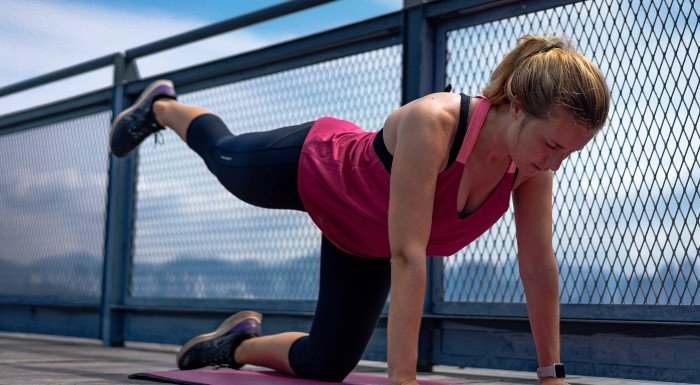 woman stretching outside on bridge