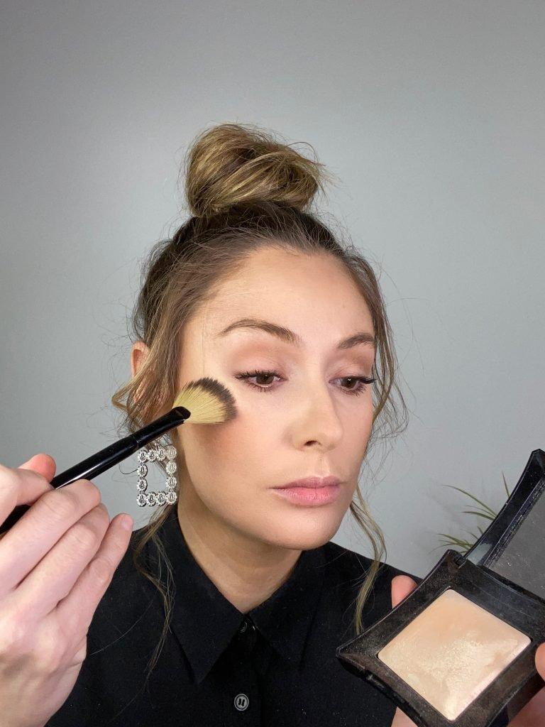 Makeup artist applying highlighter