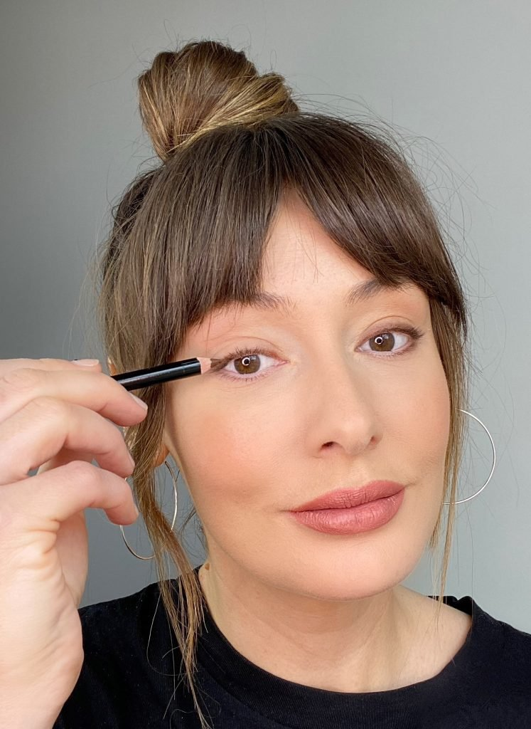 Makeup artist applying eyeliner